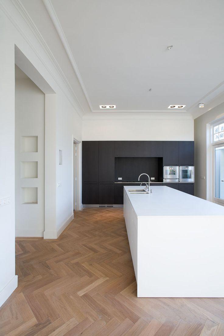 Licht houten vloer. Donker houten keukenkast en spierwit kookeiland. Mooie combinatie.