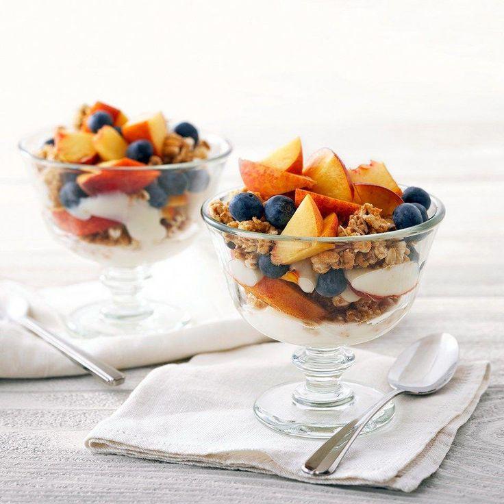 Schichten von aromatisiertem Joghurt, knusprigem Müsli, Pfirsich und Blaubeeren …