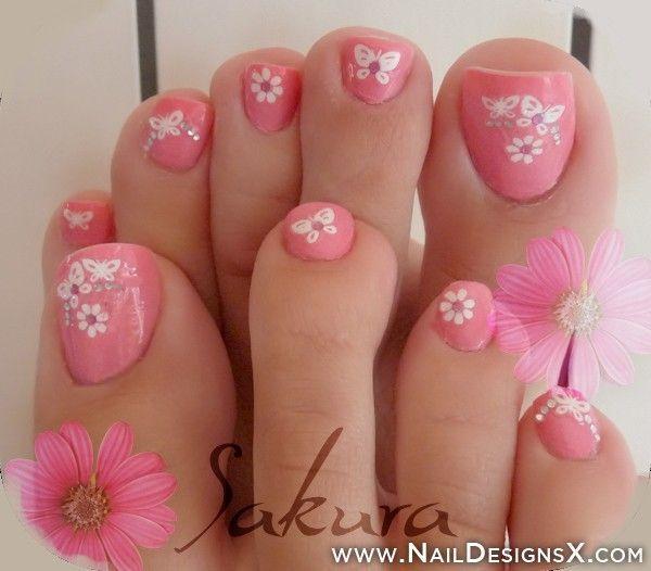 Pink toenail art design with daisy flowers and cute butterflies