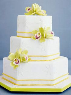 3-tiered white hexagonal cake featuring raised floral appliques, yellow-pearl trim, sugar-paste green cymbidium orchids