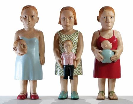 Carved and painted wood sculpture of three women standing side-by-side, each holding a figure. The figure on the left holds a head, the figure in the middle holds a small male figure, the figure on the right holds a baby.Claudette Schreuders