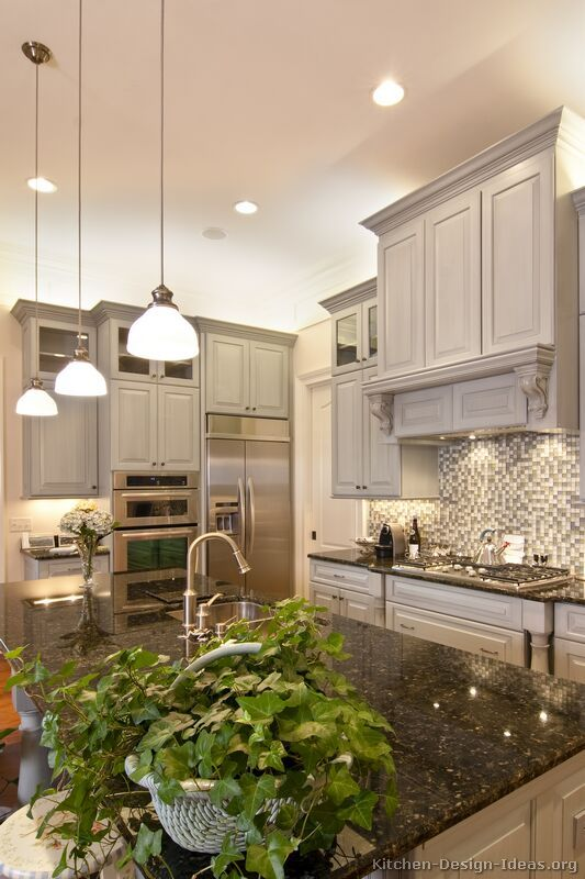 Lovely gray kitchen with island pendant lights, a wood hood, a glass tile backsplash, and high ceilings!