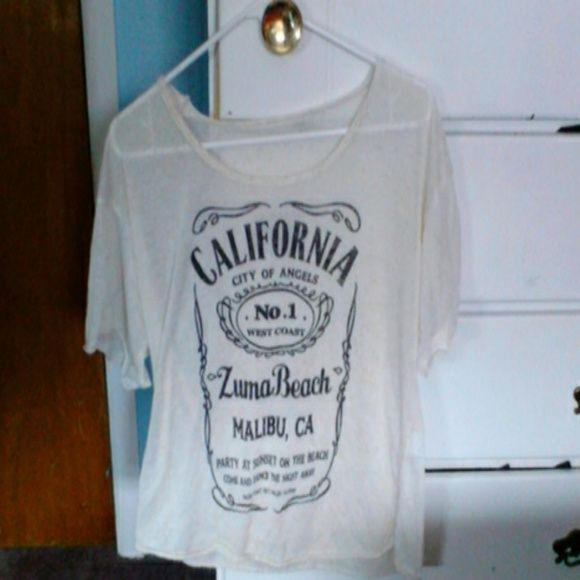 "Jack Daniels Brandy Melville T shirt SOLD Rare Brandy Melville Off white T ""California city of Angels. West coast Zuma Beach Malibu Ca,"" doesn't have a tag, bought off here and never wore it at all. Needs to find a good Brandy Mel Lover. Seems a tad bit baggy to where its cute. Brandy Melville Tops Tees - Short Sleeve"