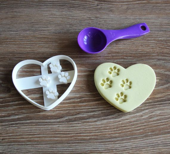 Heart With Paw Prints Cookie Cutter Dog Treat Cutter Paw print Made from Eco Friendly Material  Measurements Cookie cutters are available in two sizes. Dimensions are listed as standard inches () and its equivalent in metric (mm). The measurements are from the most outer sides of the cutter. Medium 80mmx65mm (3.14x2.56) Large 95mmx80mm (3.74x3.15)  Material Made from PLA which is a biodegradable plastic derived from renewable resources such as cornstarch, sugar cane, tapioca roots or even…