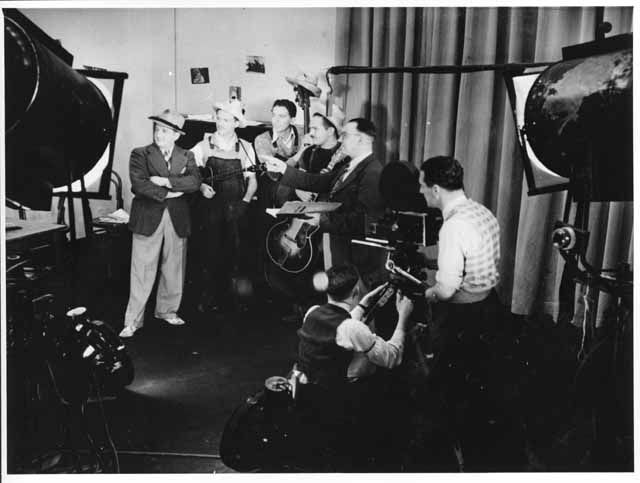 SHOW BUSINESS : PRODUCTION SHOT OF TWO MEN OPERATING A CAMERA AND FIVE MEN STANDING IN A GROUP LOOKING LEFT