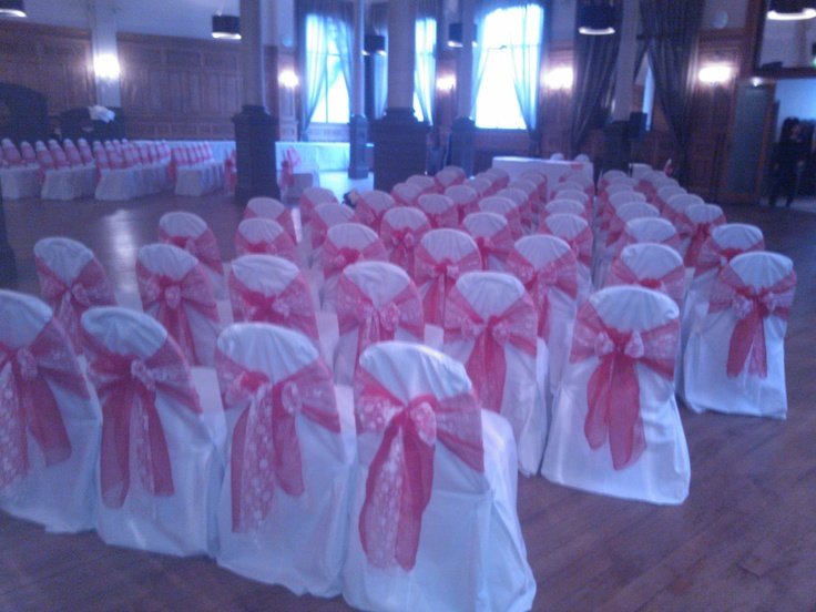 Red sashes with lace inserts on white chair covers. A Christmas wedding