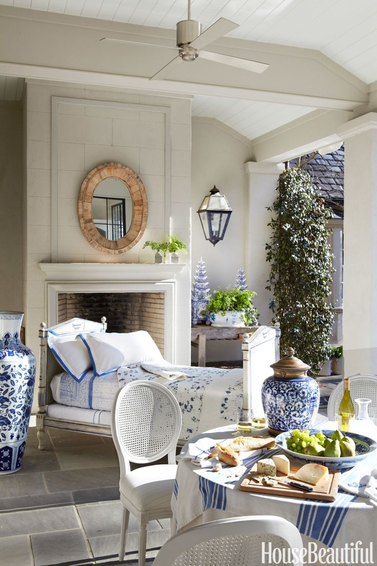"""There's nothing like sleeping in the great outdoors. In an Atlanta, Georgia, house decorated by Beth Webb, the loggia — """"an homage to blue and white"""" — opens to the pool and garden. Webb painted Victorian side chairs white and arranged them around a draped table for alfresco dining. The antique French daybed is dressed with French linens. - HouseBeautiful.com"""