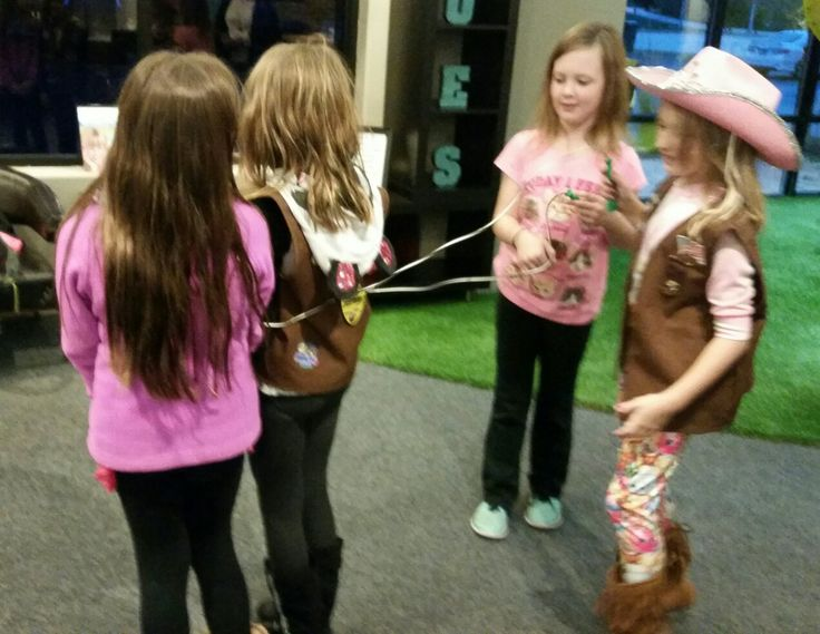 Brownie Girl Scouts learn how to floss while earning their My Best Self badge at Grand Dental.
