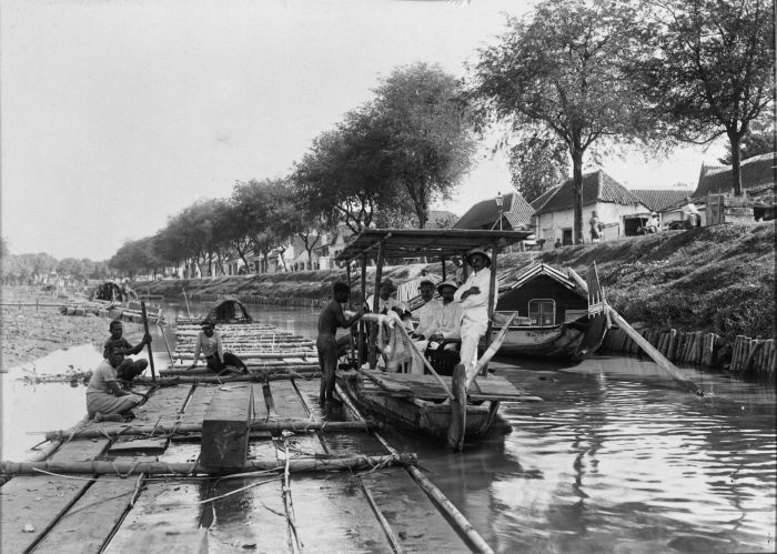 Boot met Europese mannen langszij een vlot in een kali van Soerabaja (Kali Paneleh) 1911 (Collectie Tropenmuseum)