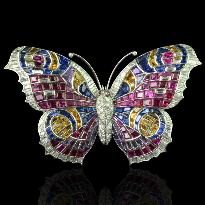 """Beautiful multi-gem brooch designed as a Peacock butterfly in ruby, diamond, amethyst and blue and yellow sapphires with a diamond-set body and further diamond highlights. Circa 1935."""