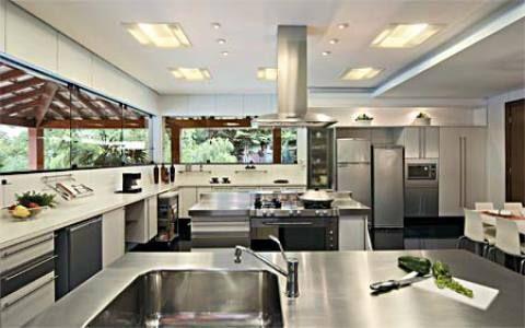 Esta cozinha gourmet prima pela elegância, como se vê nos acabamentos: quartzito preto absoluto no piso e no balcão e aglomerado sintético na bancada. Duas ilhas centrais, uma para cocção e outra para lavagem de louça, facilitam o trabalho do mestre-cuca. Projeto de Cristina Menezes.
