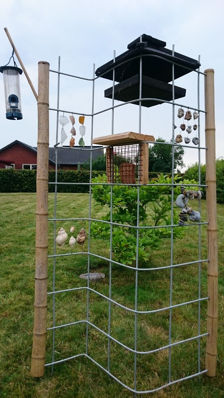 bird feeding station of welded mesh bent in S-shape with bamboo poles, beach glass, shells and adder stones  as decoration