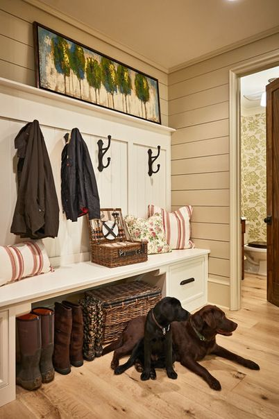 Traditional mudroom featuring wood floors, iron hooks, shiplap storage design along the wall and door leading to a powder room | New Old, LLC