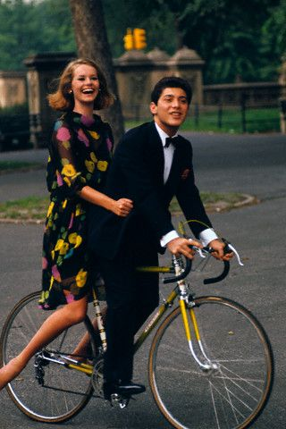 Central Park, NY November 1964 - Singer Paul Anka riding a bicycle in Central Park with model in a floral print dress - photo by Jerry Schatzberg