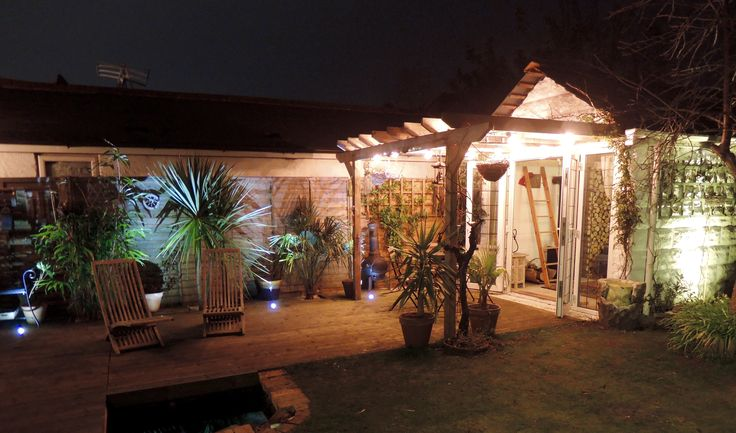 Asian style tropical decking garden with green LED uplighting and pagoda with outdoor edison filament bulbs.