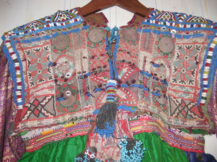 Koochi Woman's dress. The Kochi are nomadic herders and gypsies and their clothing is particularly flamboyant. Their dresses, brought back to the West, are those that identified Afghanistan in the 1970s hippie era. This dress is of green silk with sari border. The bodice is heavily covered with coins and beadwork, including jul-i-peron discs; while these have an ancient history, the silver cording on the hem is modern.