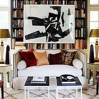 I spot sleek black marble modern obelisks framing the sofa!