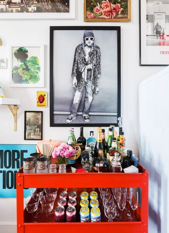 Home Bar Area With A Red Cart And An Eclectic Gallery Wall Above