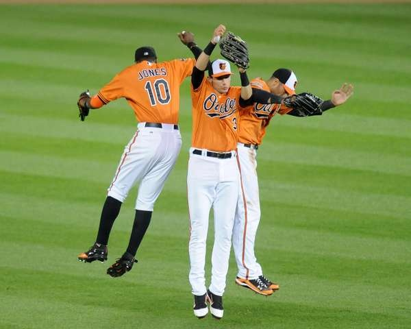 Adam Jones, Ryan Flaherty, and Nick Markakis of the Baltimore Orioles celebrate a win after a baseball game against the Tampa Bay Rays at Oriole Park at Camden Yards on May 12,
