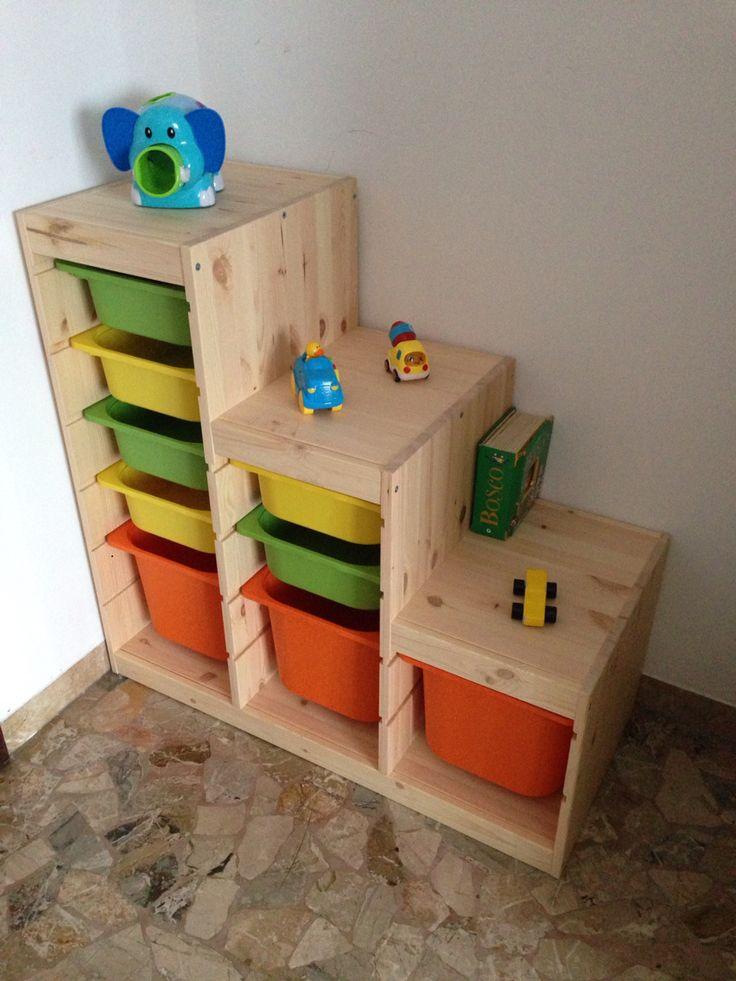 Scaffale in legno a misura di bambino. Colorato e con contenitori in plastica. Il bambino ha alla sua portata i giochi. Può usarli e rimetterli in ordine.