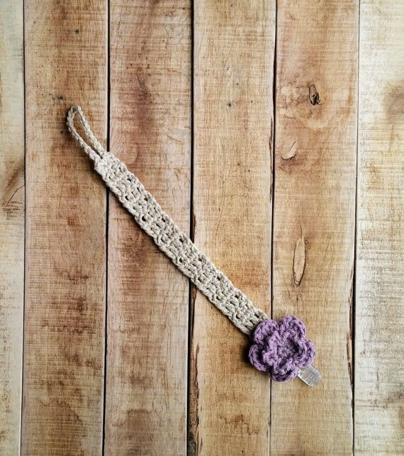 """Keep your childs soother close by with this beautiful crocheted universal soother clip/pacifier clip. Made with durable cotton yarn in tan with a beautiful purple crocheted flower embellishment.  It is made with a loop on one end that goes through any soother clip a toy. On the other end it has a sturdy clip that attaches easily to clothing that cannot be removed by child. This universal pacifier clip is approximately 14"""" long from end of clip to end of loop. Makes a great toy strap as w..."""