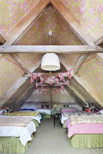 Interior designer Amanda Hornby has transformed this Cotswolds former dovecote into a house by her husband's great-grandmother. One of the jolliest rooms is this children's dorm under the eaves, papered in pink and green Manuel Canovas toile de Jouy pattern, and lined with beds. Patriotic bunting is hung to add fun to the idea of an up-and-coming sleepover.     Taken from the August 2015 issue of House & Garden.