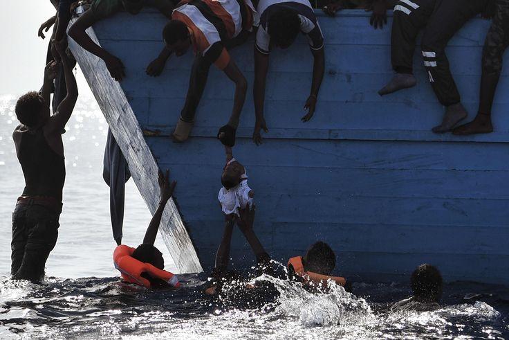 Alcuni migranti cercano di mettere in salvo un bambino in attesa dell'arrivo dei soccorsi nel mar Mediterraneo, il 4 ottobre 2016. - (Aris Messinis, Afp)