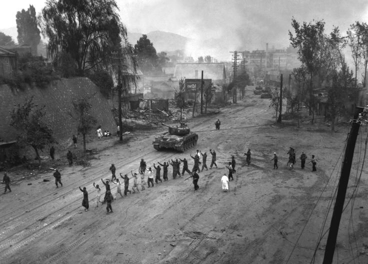 U.S. Marine tank follows a line of prisoners of war down a village street. September 26, 1950. (U.S. Department of Defense/U.S. Marine Corps/S. Sgt. John Babyak, Jr.)