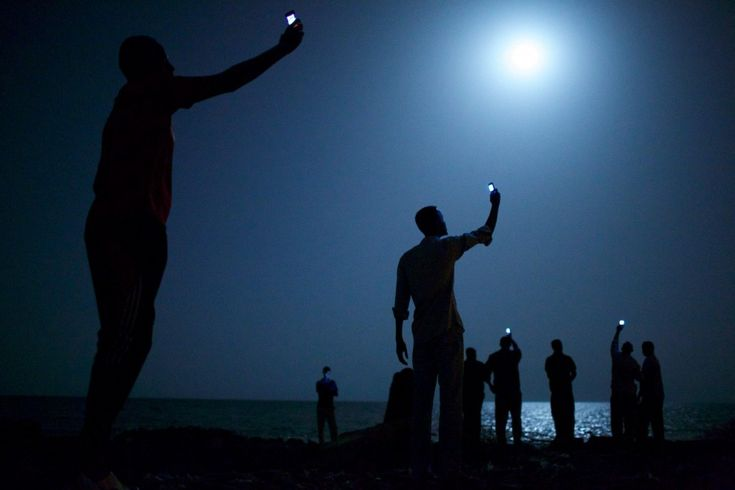 African migrants on the shore of Djibouti city at night, raising their phones in an attempt to capture an inexpensive signal from neighboring Somalia—a tenuous link to relatives abroad. Djibouti is a common stop-off point for migrants in transit from such countries as Somalia, Ethiopia and Eritrea, seeking a better life in Europe and the Middle East.