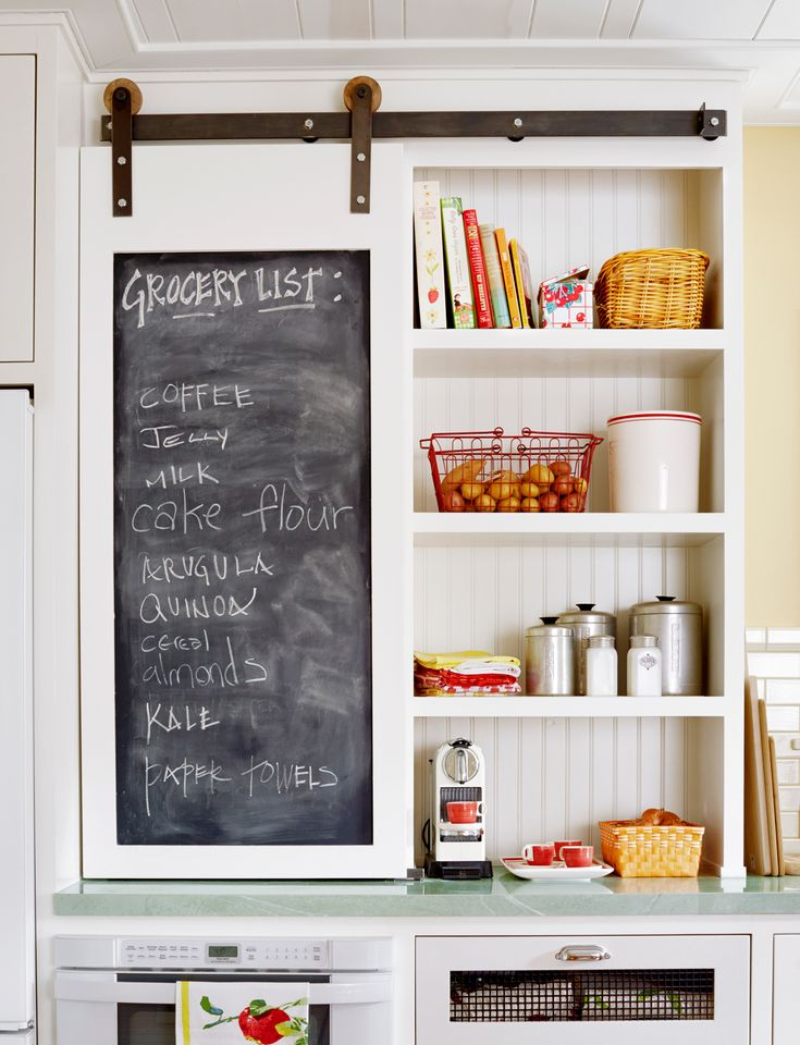 Located inside a colorful retro kitchen, this barn-style cabinet door boasts a chalkboard inset panel for keeping track of grocery lists.