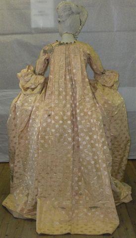 Sopravveste femminile tipologia andrienne in seta beige disegno tono su tono. Corpetto a stecche rigide e foderato. Guarnizione in seta e lamina metallica davanti e sulle maniche.