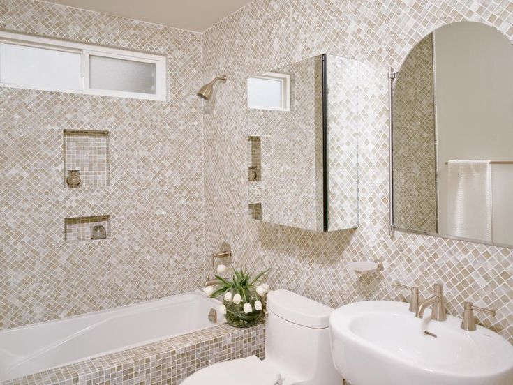 Square brown, white, beige and grey mosaic tiles have been used on the walls and around the bathtub in this small bathroom. An arched mirror, medicine cabinet, pedestal sink and toilet are also in the room. In the shower, two built-in shelves providing plenty of storage.