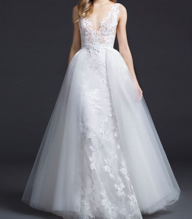 PRICE: $4,400.00  Ivory Venice lace trumpet bridal gown with overskirt, V-neckline front and back, detachable tulle skirt with lac appliqué at natural waist, chapel train.