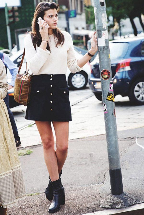 Street style de look trendy com saia preta de botões, tricot e bota.