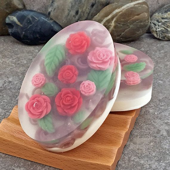 A unique handcrafted goat milk soap featuring small soap roses in 3 shades of red and pink atop green leaves and a layer of soap brown soap curls