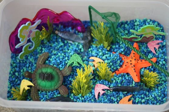 "Ocean Sensory Tub  Materials used:    Turquoise aquarium rocks  Aquarium net  Pink clam dish/scooper  Turtle (this and the starfish are toys that ""grow"" when you place them in water…we just liked the way they looked!)  Starfish  Seaweed for aquariums  Bait fish (these are extra squishy)  Foam mermaids  Foam glitter fish  2 gold coins"