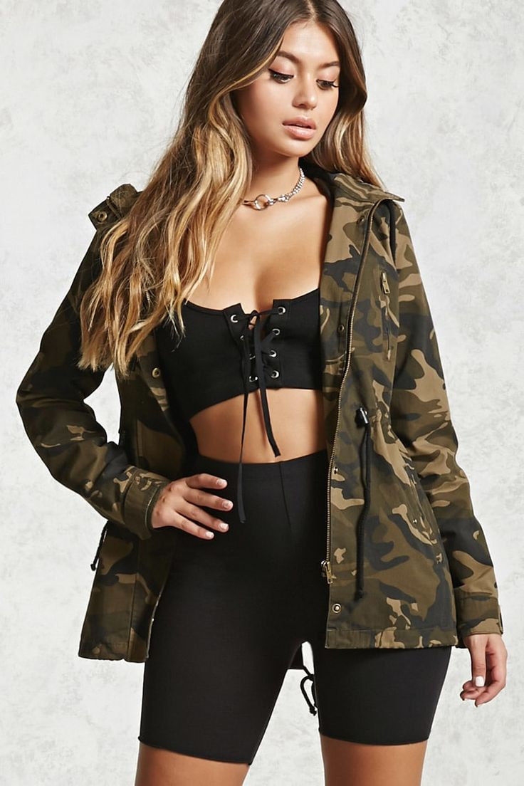 Style Deals - A woven jacket featuring an allover camo print, an attached hood with drawstring ties, front zipper with snap-buttons, front zip pocket, two front snap-button flap pockets, an adjustable drawstring waist, and a drawstring fishtail hem.