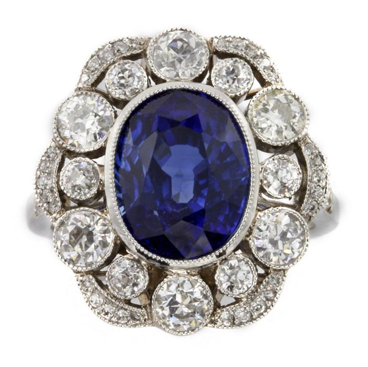 A sapphire and diamond cluster ring, the oval-shaped faceted sapphire weighing 5.17 carats, millegrain rubover-set to the centre of a cluster surround of brilliant-cut diamonds alternating in size, weighing a total of 1.45 carats, all set to a platinum mount with pierced fancy gallery, to a square-section shank with diamond-set shoulders, hallmarked platinum, London 2008, bearing the Bentley & Skinner sponsor mark.