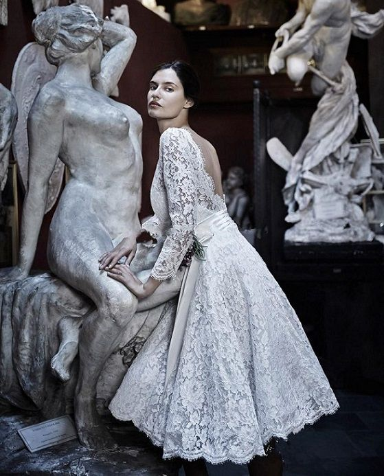 Bianca Balti with sculpture for Italian label Alessandro Angelozzi Couture, 2015 bridal collection. Photograph by Fabrizio Ferri. – Balti wears a short wedding dress with a boat neck open back, a satin bow waist sash, and ivory lace sleeves. Balti impresses in dreamy fairy-tale silhouettes and more sexy and modern form-fitting shapes…