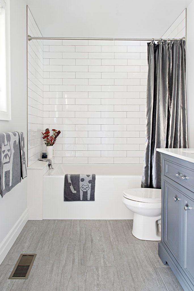 Blue-grey bathroom vanity with white subway tiles …