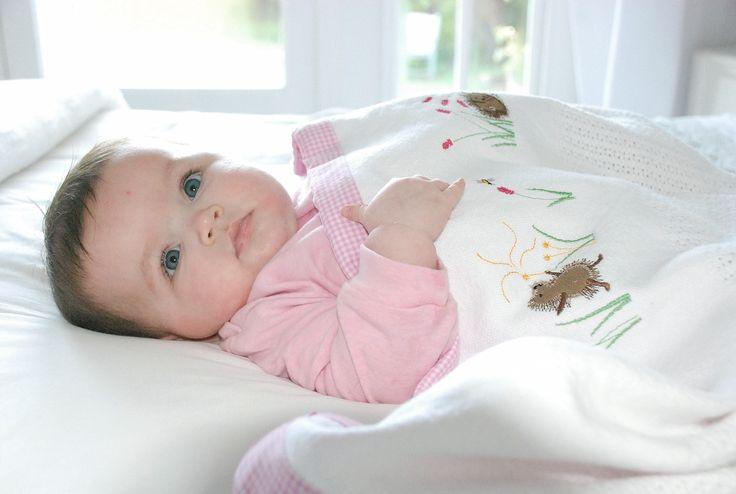 Baby Jordan snuggling under her girl hedgehog cotton cell blanket from the Tom & Bella range.