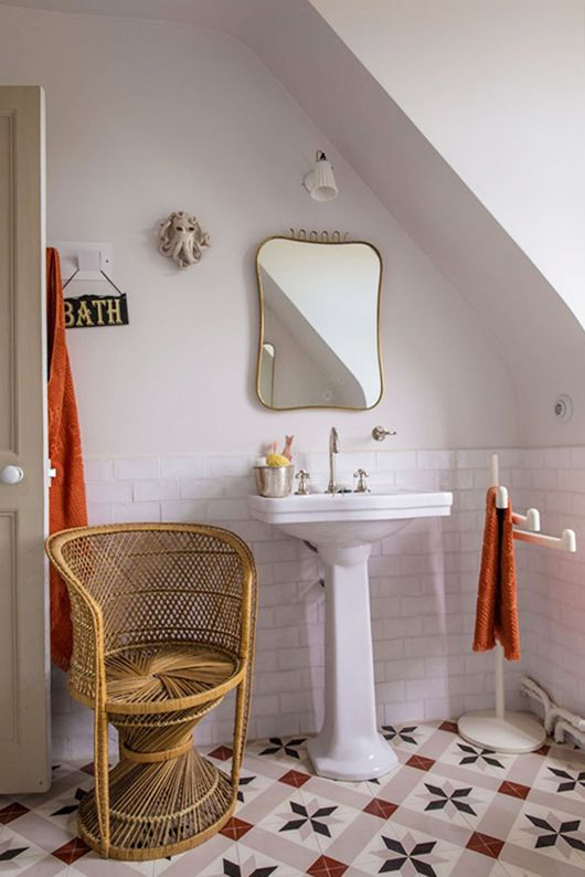 Adorable white bathroom with a hint of pink on the floor titles.