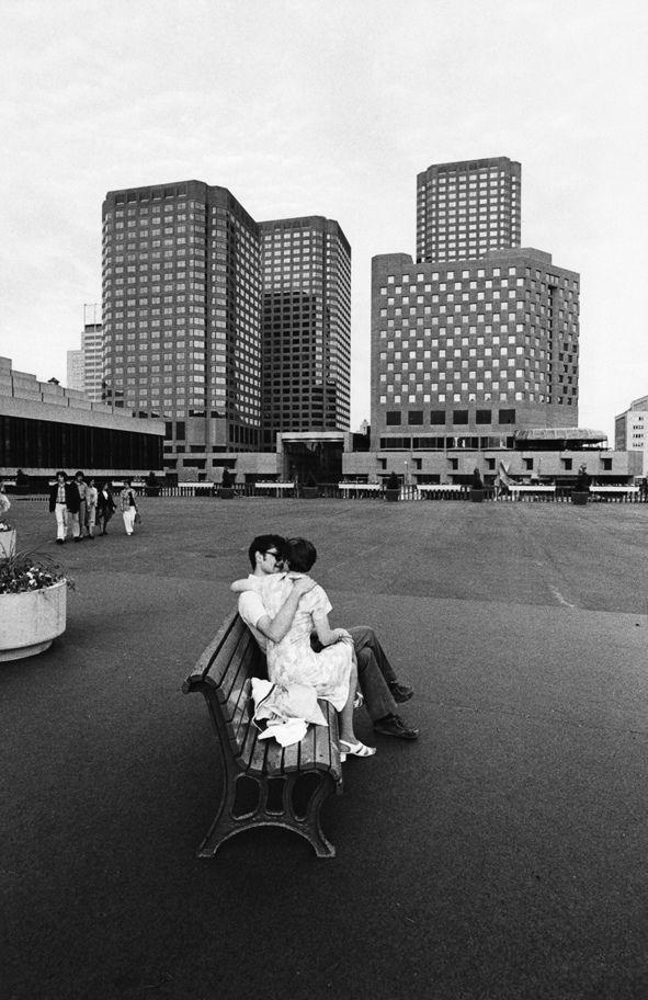Mario De Biasi, grande fotografo di baci e abbracci, non poteva lasciarsi sfuggire questi due innamorati seduti su una panchina di una piazza di Montreal. Le panchine attraggono gli innamorati, che insieme attraggono gli sguardi di fotografi e non fotografi. L'amore trova nella panchina lo spazio ideale ed emozionante della sua rappresentazione pubblica.