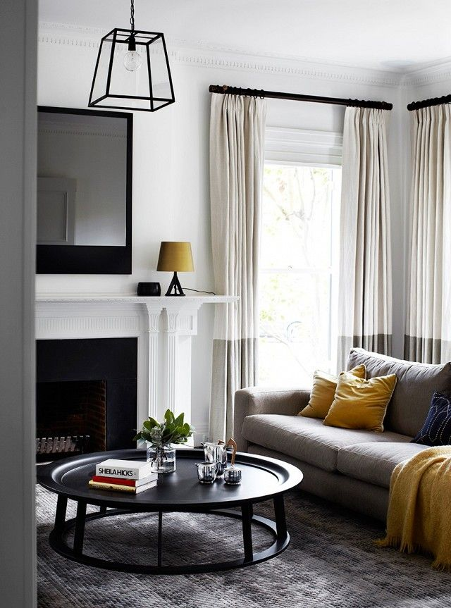 Dramatic living, with a custom made fireplace mirror, a lantern, and pops of yellow