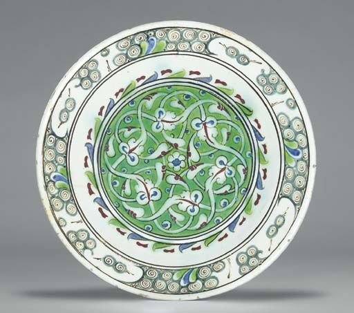 AN IZNIK POTTERY DISH OTTOMAN TURKEY, CIRCA 1630 With sloping rim on short foot & of shallow form, white interior decorated with large roundel of densely entwined white foliate tendrils with red highlights around a small central rosette, all reserved on green ground, within triple black ring radiating blue & green stripes with red motifs in the interstices, rim with grey stylized wave & rock motif with green & blue highlights between further black rings... 10¼in. diam.