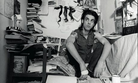 Nick Cave in West Berlin, August 1985: 'Nick spent much of the mid-1980s writing his first novel, And the Ass Saw the Angel. He decorated the walls of his retreat – a tiny closet in a prewar apartment – with tokens and fetishes.'  Photograph: Bleddyn Butcher