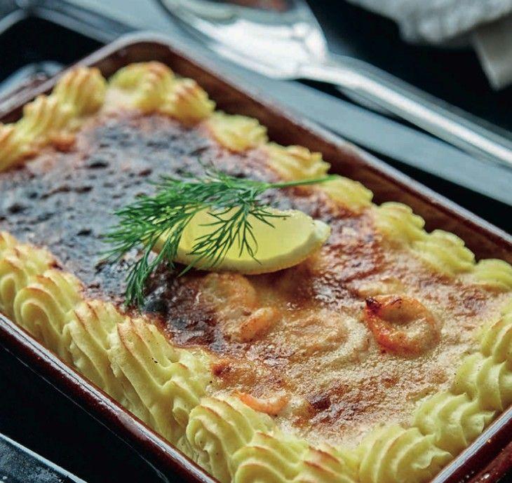 Klassisk gratäng med fisk och räkor i vitt vin i en ram av vackert spritsad pommes duchesse.