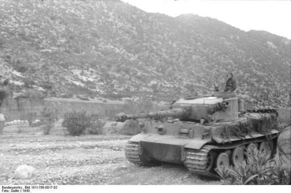 """Char tigre I en Tunisie. Ce nouveau char lourd donne un impact fort aux attaques allemandes, les alliés ne possédant rien d'équivalent en face. Ils sont cependant en nombre très faible et ont encore des """"maladies de jeunesse"""" qui l'handicape dans son utilisation, laissant encore une fois la responsabilité principale des combats aux vieux panzer III et IV."""