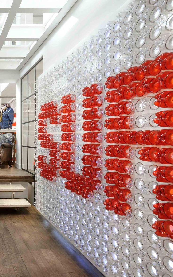 Plastic Drink Bottles Were Reused To Create A Giant Logo For This Office. The large red and white logo is made from over 900 bottles that are backlit, making it appear more like a piece of contemporary artwork than a typical company logo.