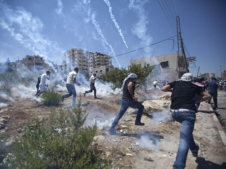 Palestinians run for cover during clashes with Israeli soldiers